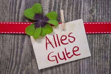 Kleeblatt mit Karte, rotem Band auf Holzhintergrund Alles Gute