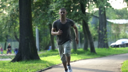 Young man jogging in city park, super slow motion, 240fps