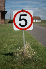 A five miles per hour sign on a grass verge