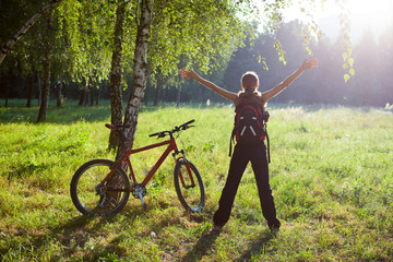 Excited girl cyclist standing in a spring park with hands outstr