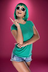Trendy modern young woman pointing up