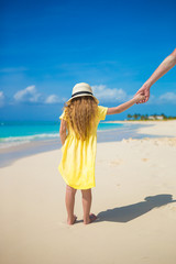 Adorable little girl in hat holding father hand at beach