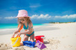 Adorable little girl playing with toys on beach vacation