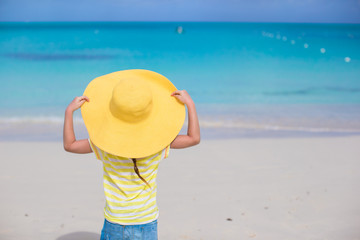 Little girl in a big yellow straw hat on white sand beach