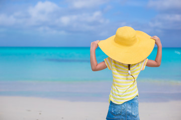 Rear view of little girl in a big yellow straw hat on white sand
