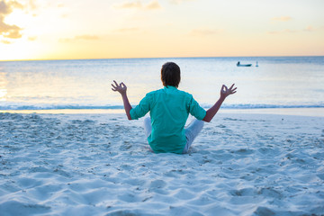 Young man sitting in lotus position on white sand beach
