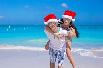 Young happy couple in red Santa hats on white beach