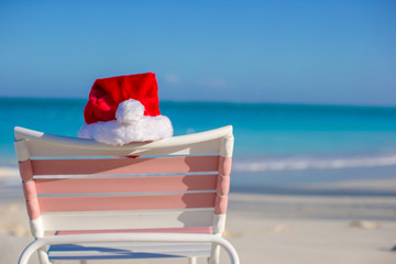 Close up Santa hat on chair longue at tropical beach