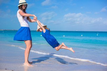 Happy mother and her adorable little daughter enjoy summer