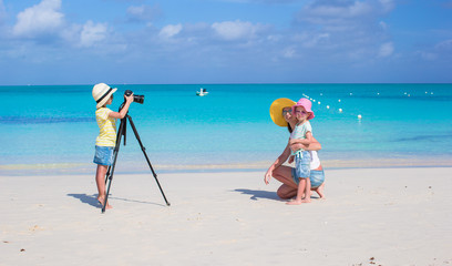 Little girl making photo of her mom and sister at the beach