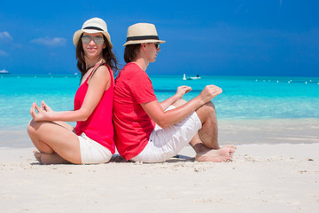 Happy lovely couple in lotus position on tropical white beach