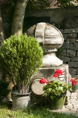 Corner of old garden with stonework, plants and flowers