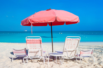 Cute umbrellas and sunbeds at tropical beach