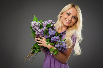 blonde girl in purple dress holding bouquet of lilac