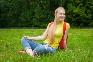 blonde girl out in the open air wearing jeans and bag