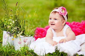 cute newborn girl smiling on grass in pink skirt with flower
