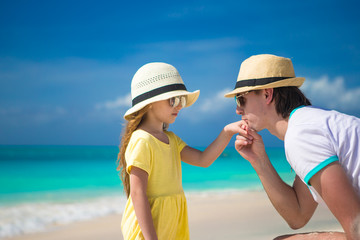 Happy dad kisses the hand of his little daughter on beach