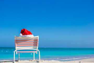 Red Santa hat on chair longue at sea shore