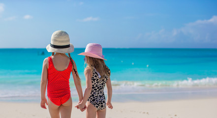 Back view of two little girls looking at the sea on white beach