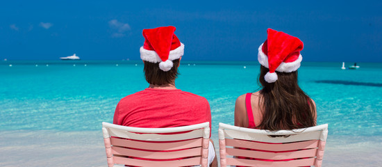 Back view of young couple in red Santa Hats sitting on beach