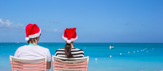 Back view of young couple in Santa hats enjoy beach vacation