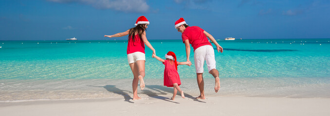 Happy family of three in Christmas Hats having fun on white