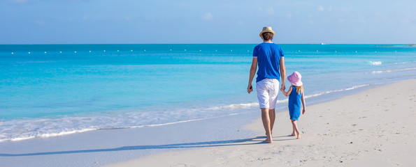 Little adorable girl and her father walking along the sea