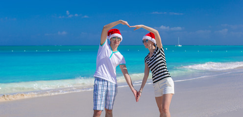Portrait of young couple in Santa hats enjoy beach vacation