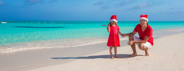 Young father and adorable little daughter in Christmas Hat at