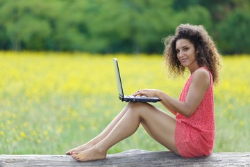 Pretty barefoot woman working on a laptop