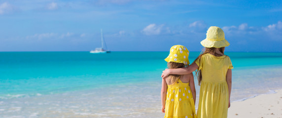 Back view of two little cute girls looking at the sea on white