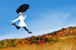 Young woman jumping with holding umbrella