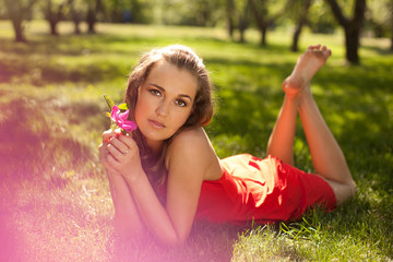 girl wearing red dress lying on the grass
