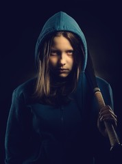 Teen girl in hood with baseball-bat