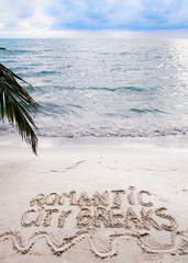 Romantic City Breaks message written on sand, vacation concept