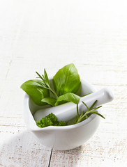green herbs in a mortar and pestle