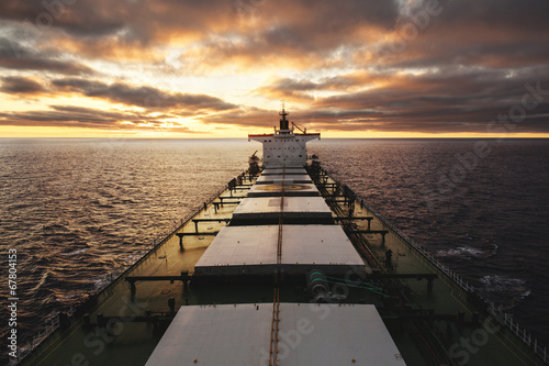 Leinwanddruck Bild Cargo ship underway at sunset
