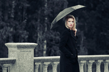 Sad young fashion woman with umbrella in the rain