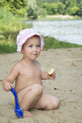 Little funny girl sits on the sand near the lake in summer and s