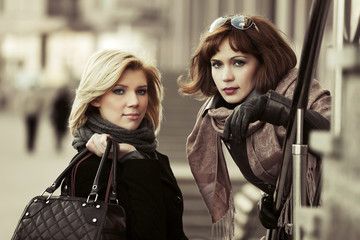 Two happy young fashion women on the city street