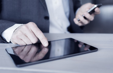 Businessman using tablet pc and smartphone