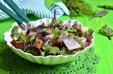 Salad with herrings,bread and beet tops.