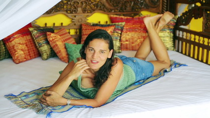Woman lying on oriental bed and talking to the camera