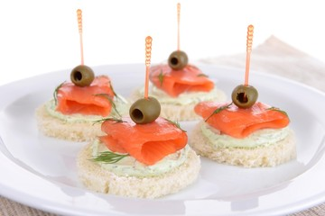 Delicious canapes on plate close-up