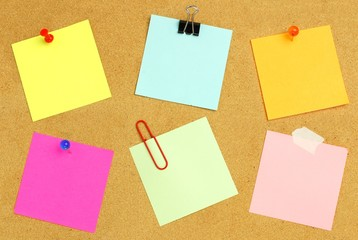 Sticky notes of various colors and fasteners on a bulletin board