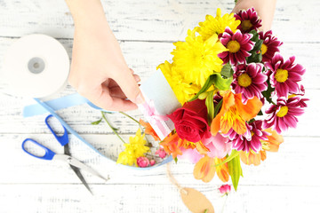 Female hands composing beautiful bouquet, close-up. Florist at