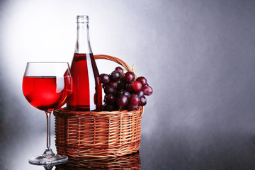 Ripe grapes, wine glass and bottle of wine on grey background