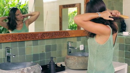 Woman brushing and tie hair in the bathroom
