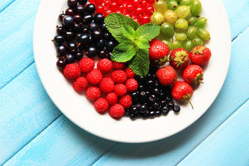 Forest berries on plate, on color wooden background