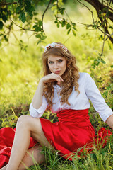 woman wearing red skirt sitting under the tree